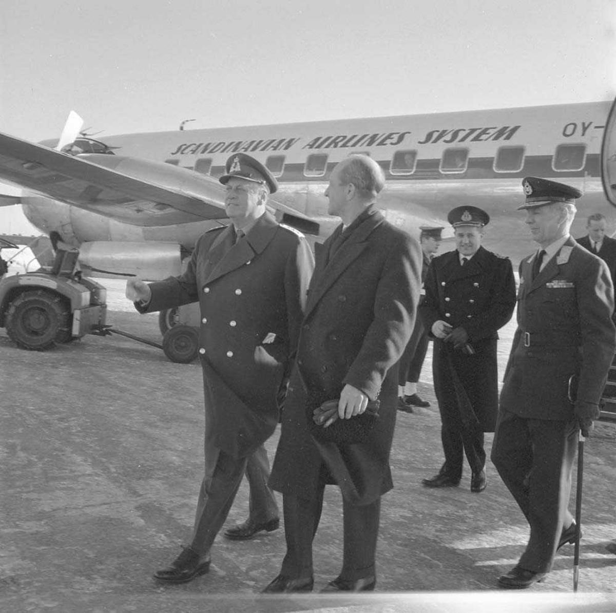 H.M. Kong Olav V besøker Bodø flystasjon før han drar videre til Bardufoss flystasjon. Flyet i bakgrunnen er en Convair Metropolitan 440.