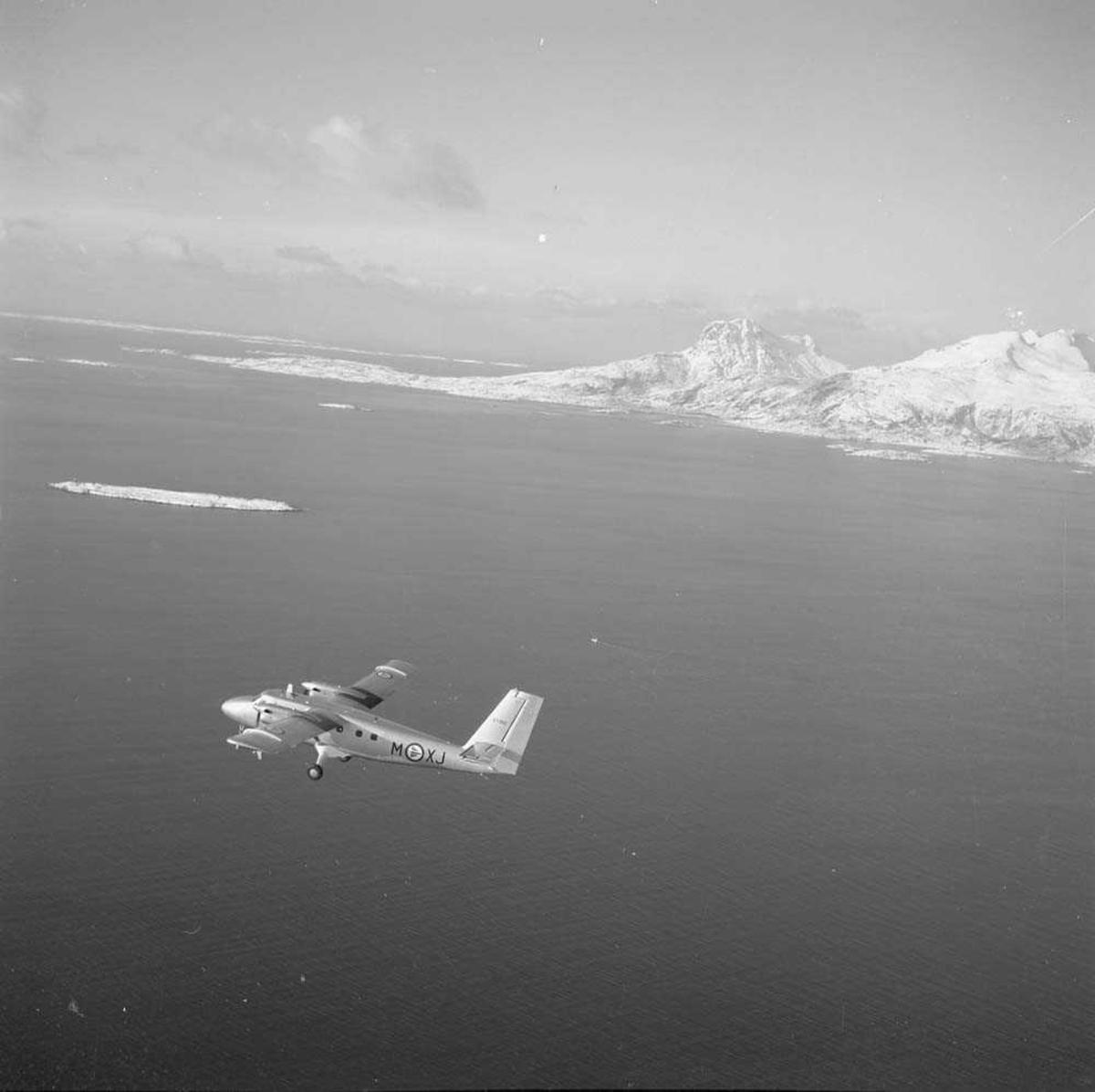 Twin Otter, kjennemerke XJ-M,  tail nr. 67 062, flyr i Bodø-området med Landegode i bakgrunnen. Flyet tilhørte 719 skvadron på Bodø flystasjon.