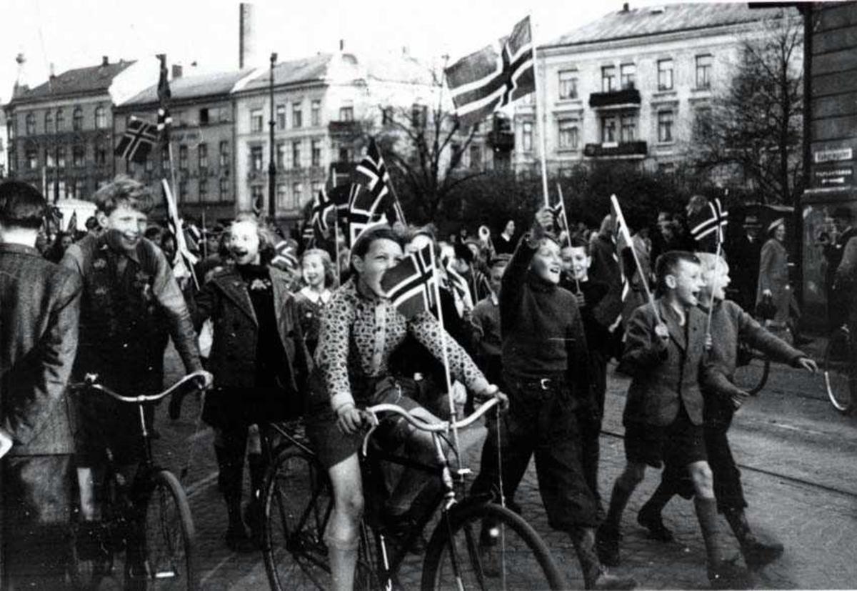 Barn som går i tog med norske flagg. Bygninger i bakgrunnen.