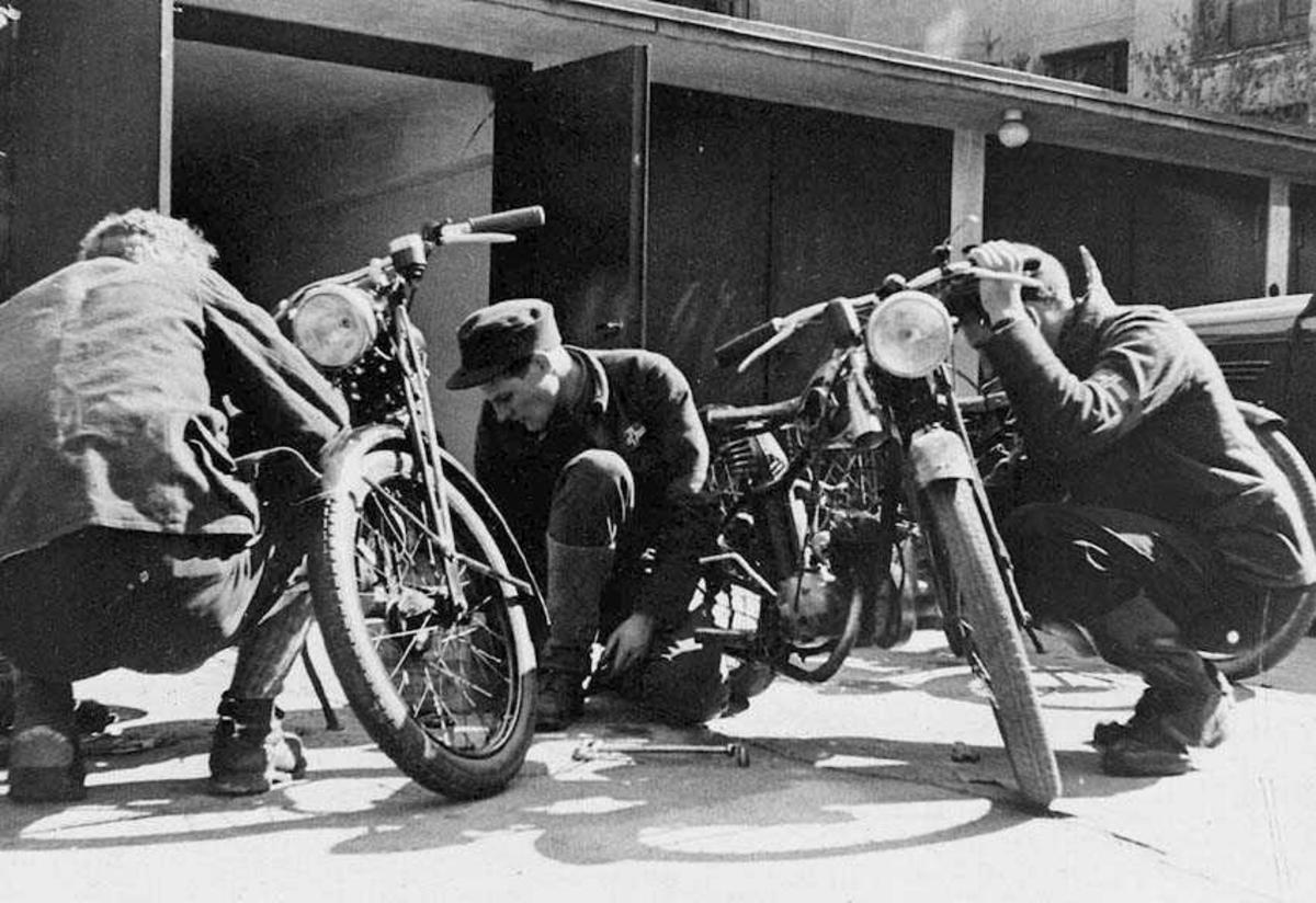 Tre personer, menn, som holder på med to motorsykkler. Bygning i bakgrunnen.