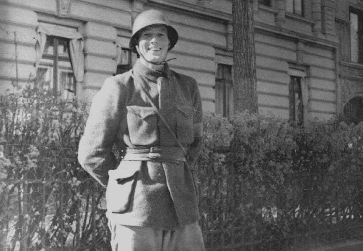 En person i uniform og hjelm, som står vakt utenfor en bygning.