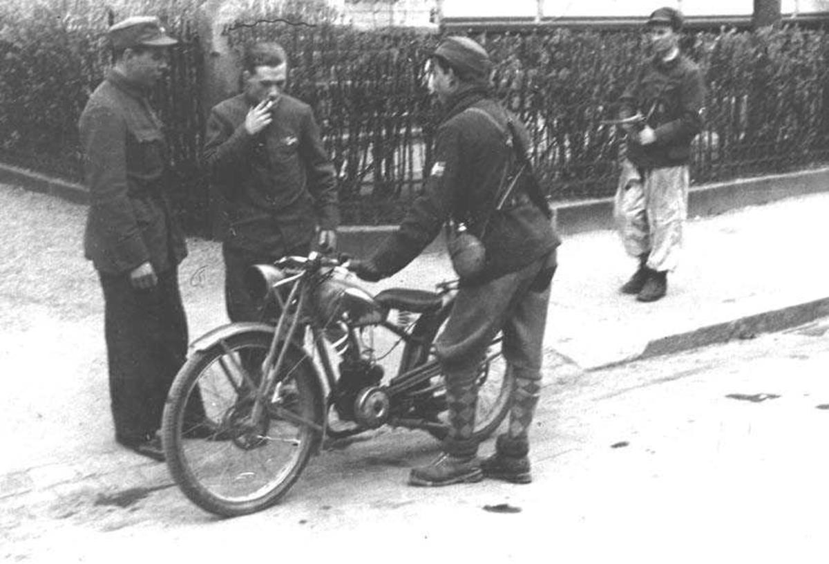 Fire personer, menn. Tre står ved en motorsykkel.