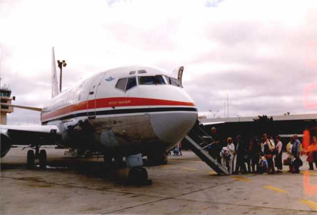 Lufthavn (Arrecife). Ett fly på bakken, Boeing 737-205, LN-SUIT fra Braathens SAFE AS. Flere persopner/passasjerer på vei ombord i flyet.
