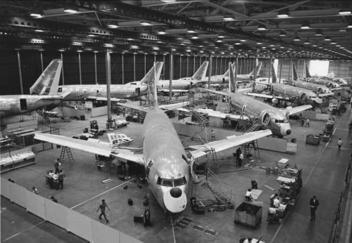 Tolv fly på bakken. Boeing 737. Under kontruksjon. Flere mennesker rundt flyene.