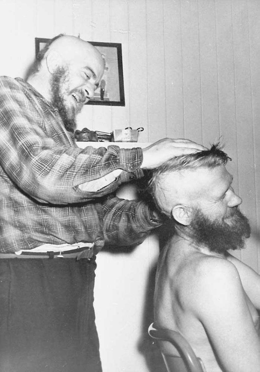 En person som steller håret på en annen person. Begge menn.