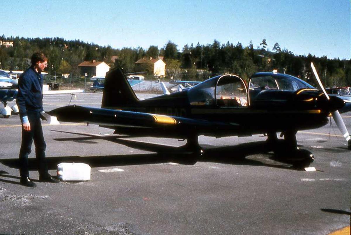 Ett fly på bakken. LN-RAC, Robin R.2160. En person ved flyet. Inspeksjon. Flere småfly i bakgrunn.
