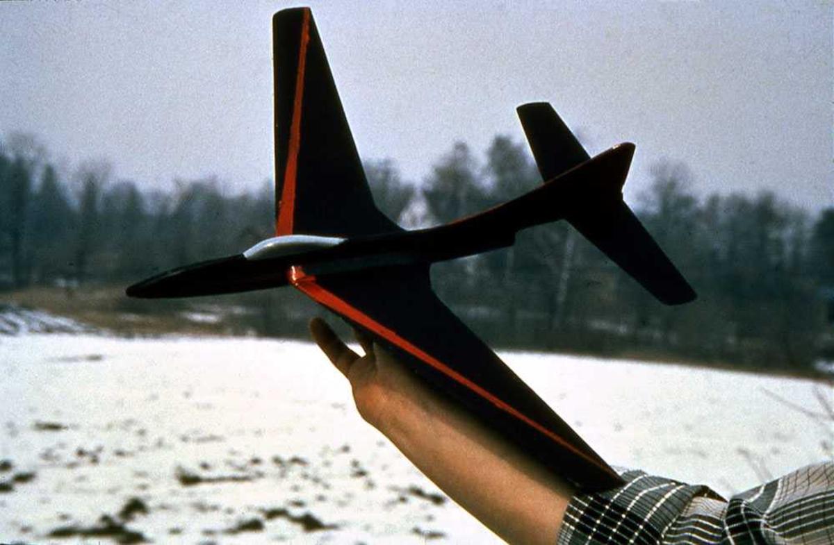 Ett modellfly holdt oppe av person. Modellens overside.