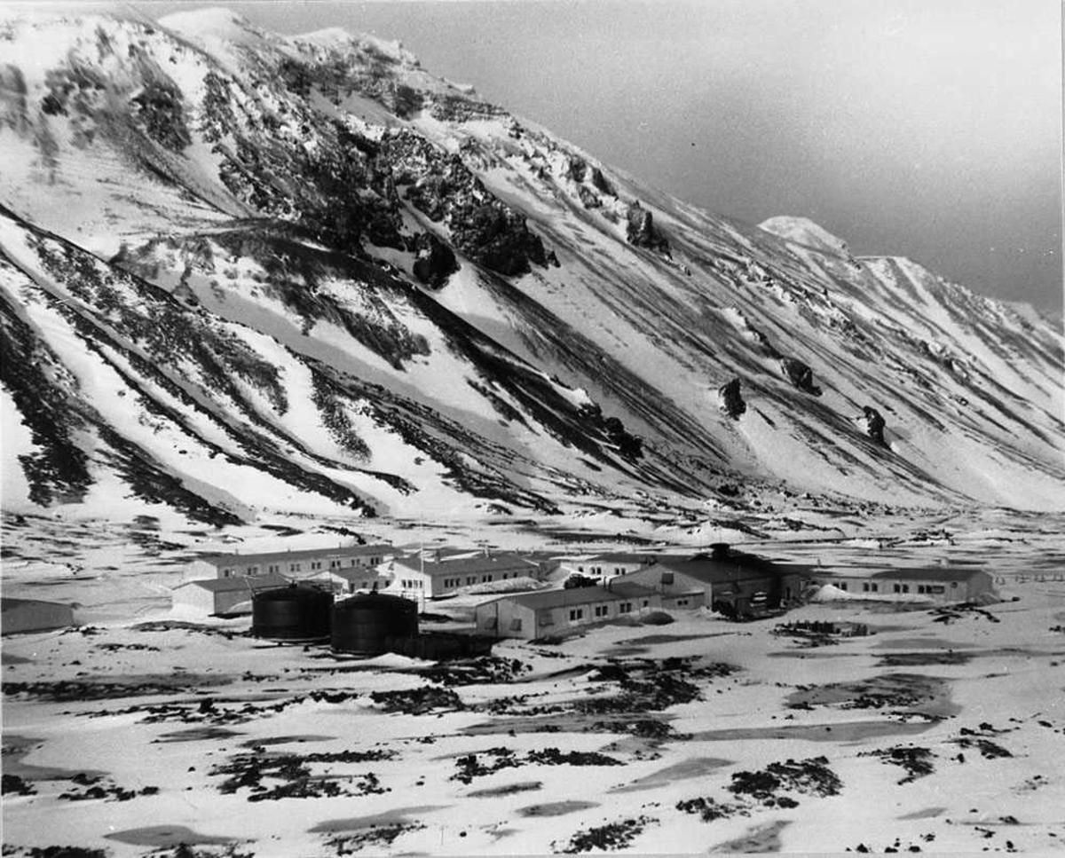 Loran stasjon med flere bygninger, Fjell i bakgrunnen. Snø på bakken.