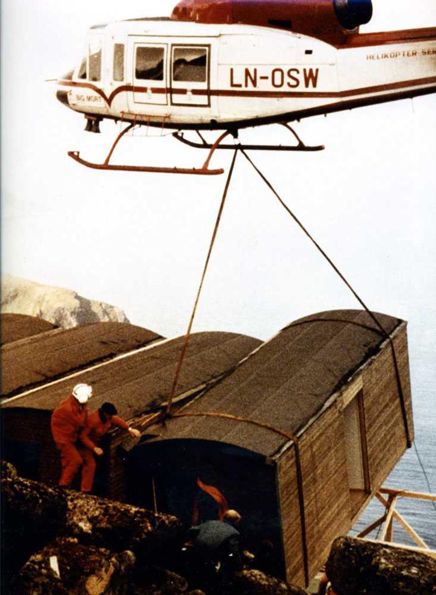 Ett helikopter i luften som løfter/plasserer en anleggsbrakke, LN-OSW. Tre personer ved  brakken. Flere brakker som står ved siden av.