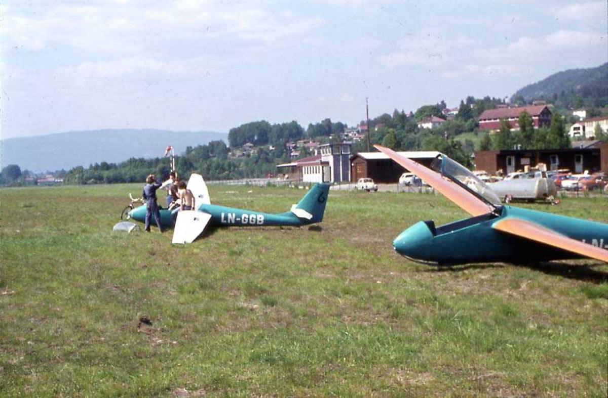 Lufthavn. To seilfly på bakken, PIK 16 Vasama og MuchaStd. Flere personer ved det ene seilflyet. Bygninger i bakgrunnen.