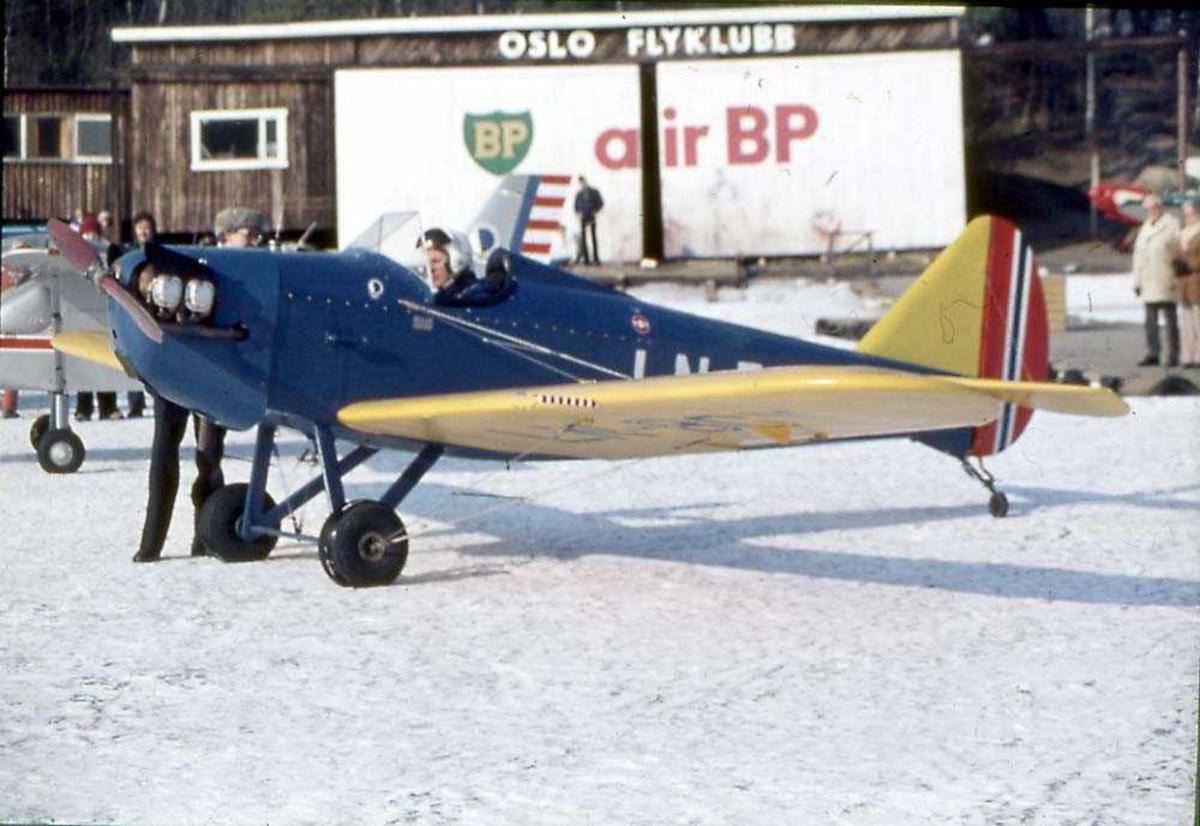 Ett fly på bakken, Bowers Fly Baby 1-A, LN-BGY. En person sitter i cockpiten. Flere personer og.en bygning i bakgrunnen.