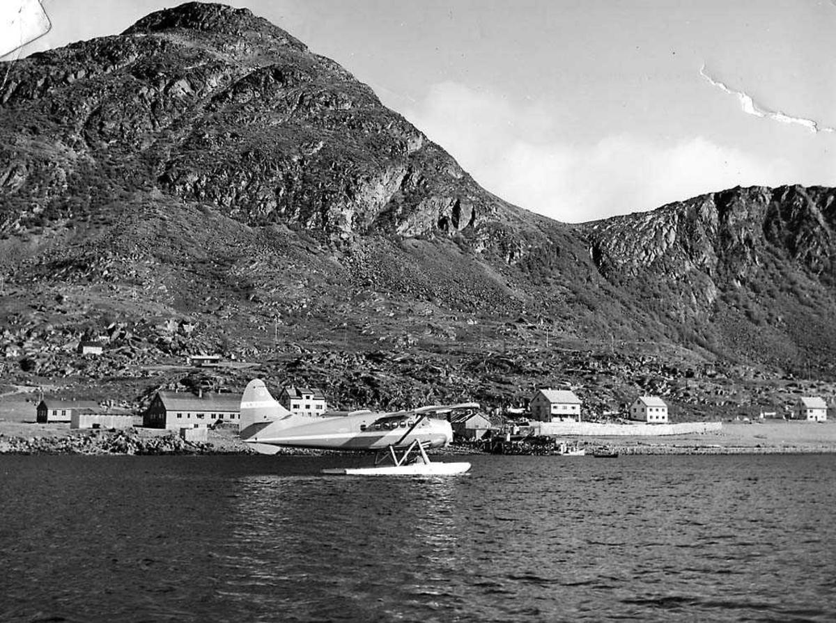 Ett fly på vannet, DHC-3 Otter LN-SUV fra Widerøes Flyveselskap. Bygninger og fjell i bakgrunnen.