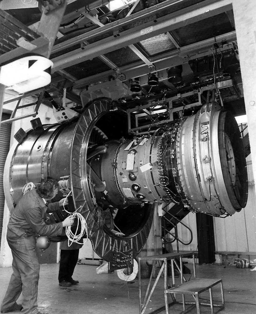 En flymotor inne i en bygning, Rolls-Royce RB 211-535C. En person som arbeider på motoren.