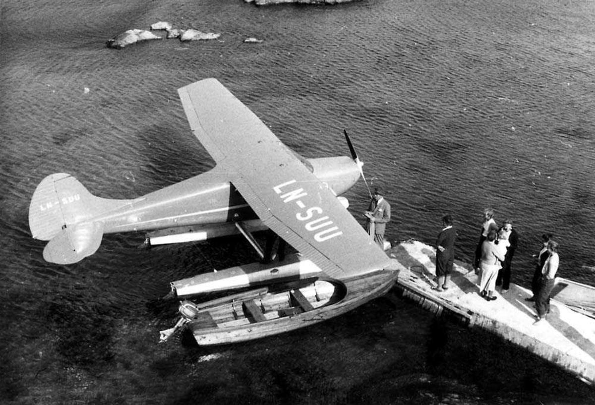 Ett sjøfly som ligger ved en kai, Cessna 170A LN-SUU fra Widerøes Flyveselskap & Polarfly. En liten båt ligger ved flyet. Flere personer på kaien.