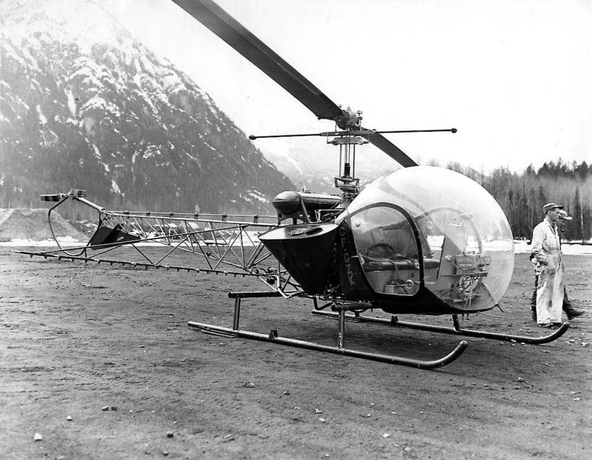 Ett helikopter på bakken, Bell 47 D-1 CF-GZK. To personer bak helikoptret. Fjell i bakgrunnen.