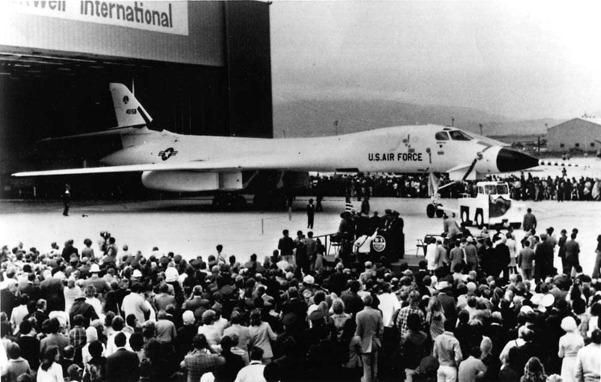 Ett fly som blir kjørt ut av en hangar, Rockwell B-1 Lancer. Folkemengde foran og bak flyet.