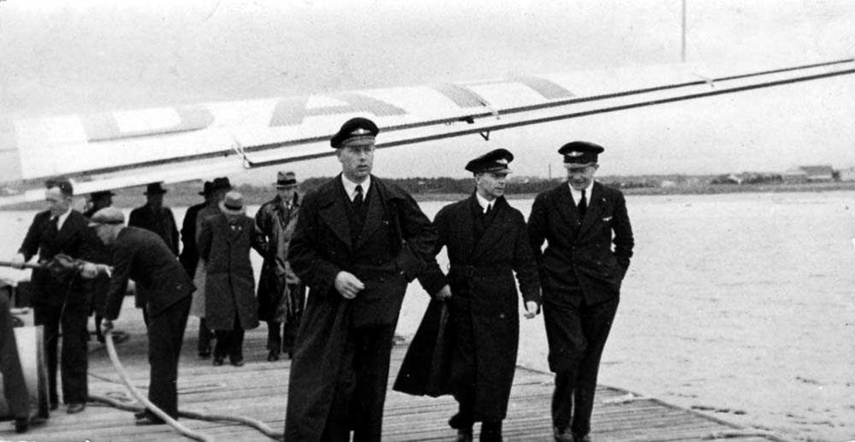 Portrett. Tre personer i pilotuniform på en sjøflyhavn. Flere andre personer og vingen til en Junkers Ju 52 i bakgrunnen.