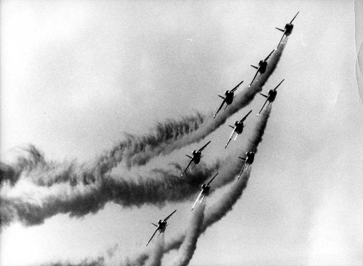 Luftfoto. Ni fly i formasjon i luften, Folland Fo.141 Gnat fra Red Arrows. Fem av flyene sender ut røyk etter seg.