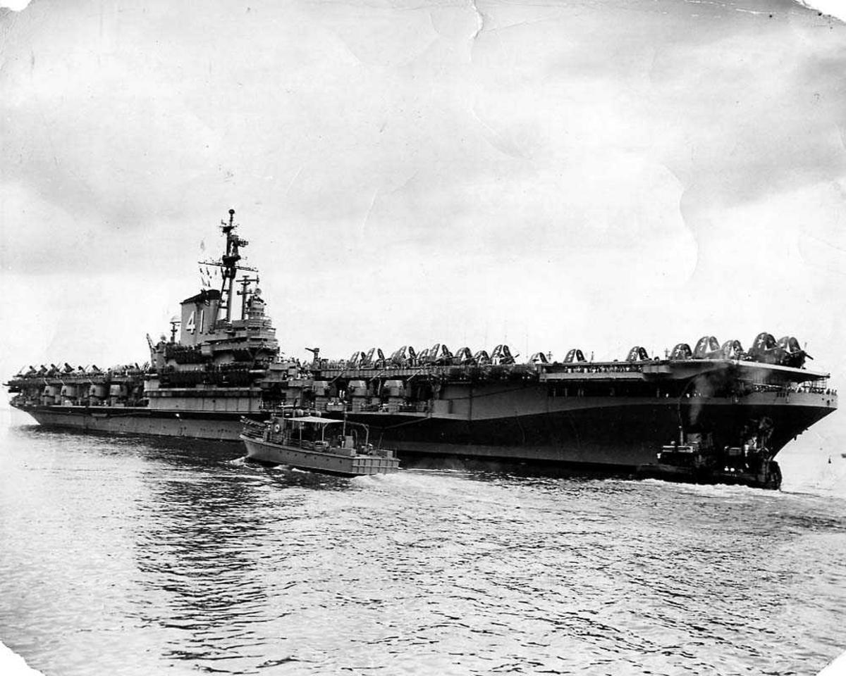 Ett hangarskip, USS Midway. Flere fly med oppslåtte vinger på dekket. En liten båt i sakte fart foran hangarskipet.