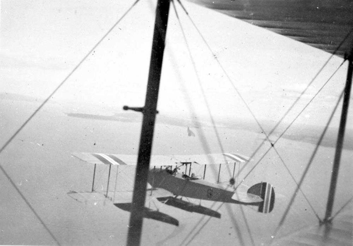 Luftfoto. Ett fly i luften som flyr formasjonsflyving. Bildet tatt fra et annet fly.