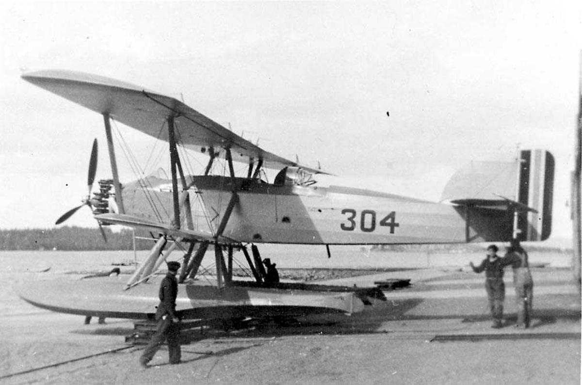 Ett fly med flotører på land, MF-11. Flere personer ved flyet.