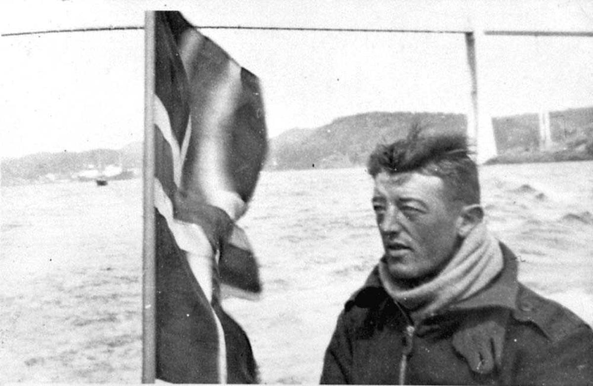 Portrett. En person, mann. Ett norsk flagg ved sidan av personen.