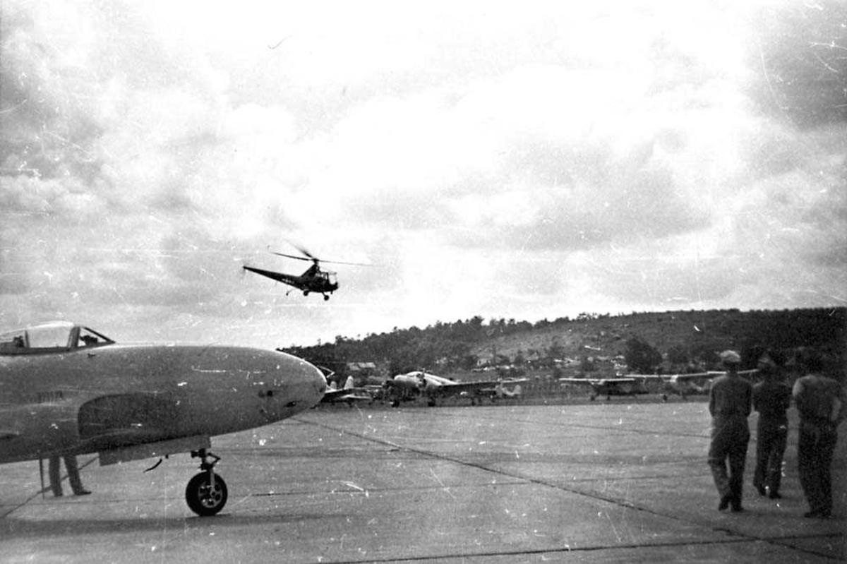 Lufthavn. Flere fly på bakken. Ett helikopter i luften. Tre personer i forgrunnen. F-80 i forgrunden.