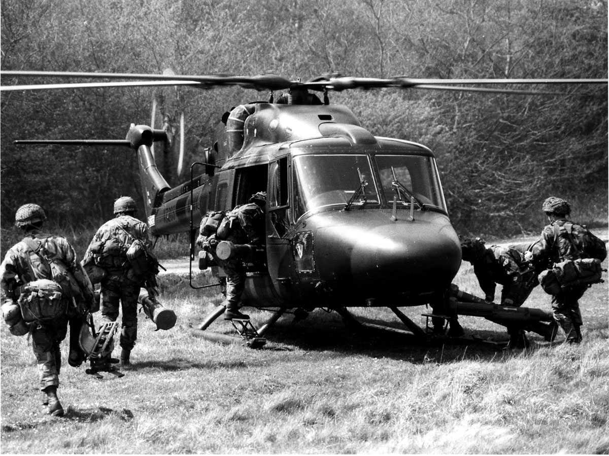 Ett helikopter på bakken. Westland Lynx AH Mk.9 tilhørende Royal Army merket XZ203. 6 soldater med full utrustning på vei inn i helikopteret. (Anti-tank)