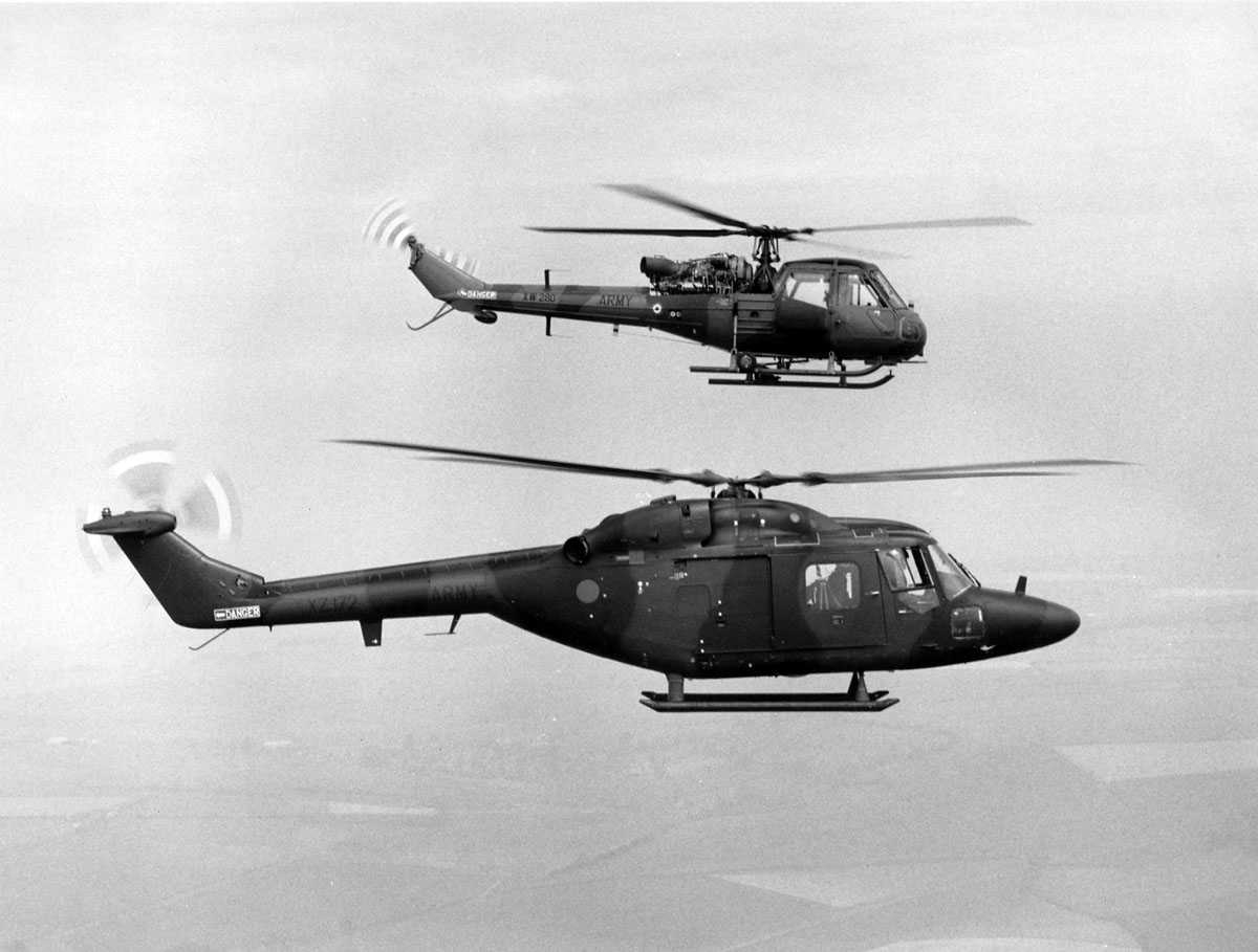 To helikoptere i luften, over landbruksområder. Westland Scout AH Mk.1 merket XW280 ARMY og Westland Lynx