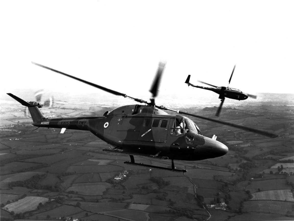 To helikoptere i luften over landbruksområder. Westland Lynx AH Mk.1  og Westland Navy Lynx prototype[?] i venstrebank.