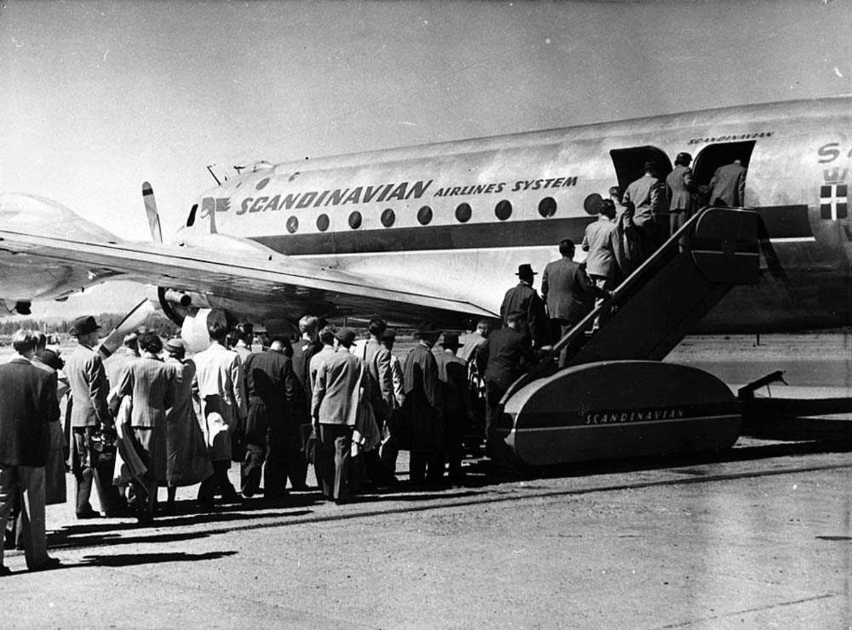 Lufthavn. Flere passasjer på vei ombord i et fly, Douglas DC-4/C-54 fra SAS.