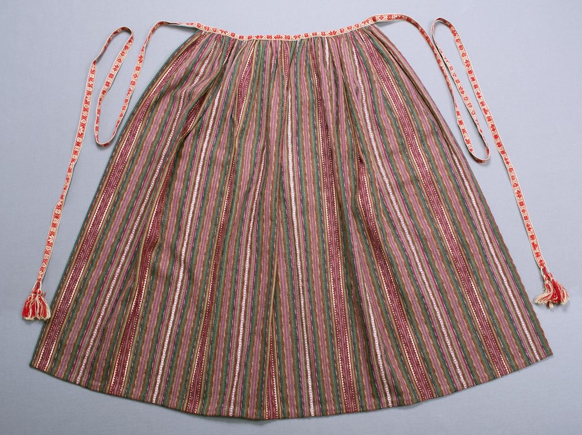 Förkläde i inslagsrips och tvist. Ränder i brunrött (vinrött), lila, grönt, blått, gult, brungult och vitt, dessutom smala flamgarnsfärgade ränder i vitt och blått och smala ränder med grått och blåsvart garn som, i ett och samma inslag, snotts om varandra för flamgarns-/ikateffekt. Förklädet är rynkat mot ett svart band som vikts om kanten, bredden upptill är 385 mm. På framsidan är det svarta bandet dolt av ett mönstrat knytband som i sin helhet är 3220 mm långt. Knytbandet är vävt i opphämta med mönster av hjärtan, stjärnor, hjärtan med krokar, kors och tulpaner/liljor i rött på oblekt linnebotten. I var ände är bandet avslutat med två tofsar som sitter på varsin ögla av tätt lindade varptrådar. Smal fåll i sidorna och 15 mm bred fåll nedtill.Varp i vitt lin- eller bomullsgarn, 9 trådar/cm. Inslag i brunrött (vinrött), lila, grönt, blått, gult, brungult och grått ullgarn samt i vitt och flamgarnsfärgat blå-vitt lin- eller bomullsgarn, ca 25 inslag/cm av ullgarnet. Bandet:Varp i rött ullgarn och oblekt lingarn. Inslag i oblekt lingarn.
