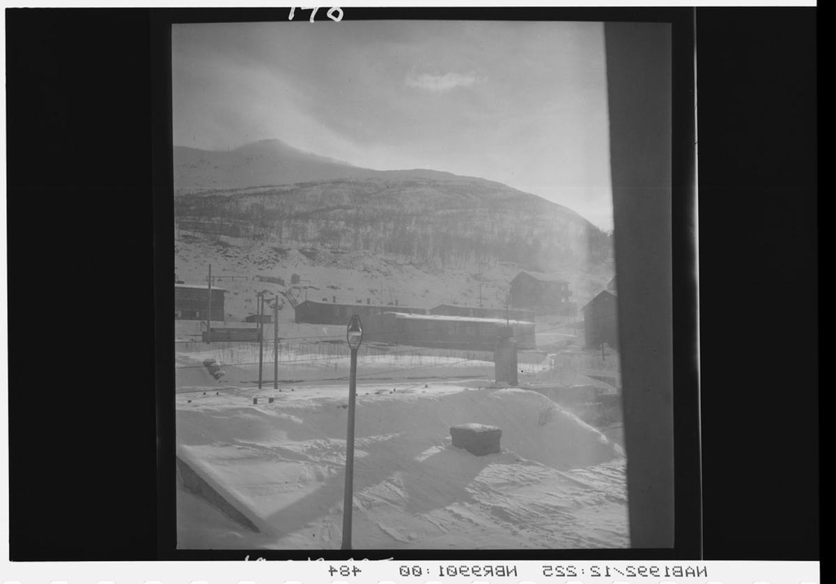 Brakker og hus ved fotenden av fjell. Vinter.