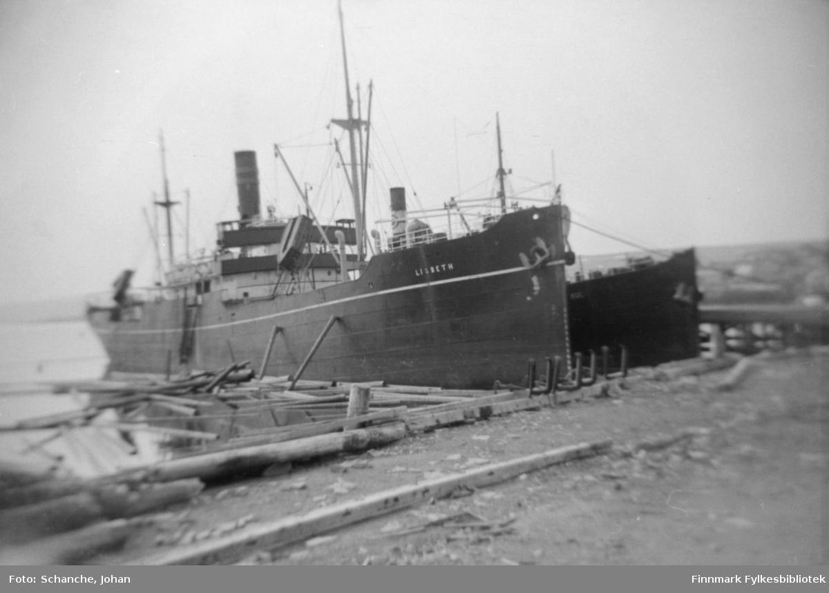 Dampskip 'Lisbeth' og en uidentifisert skip ved kai. Tømmerstokker flyter på vannet rund skipet.