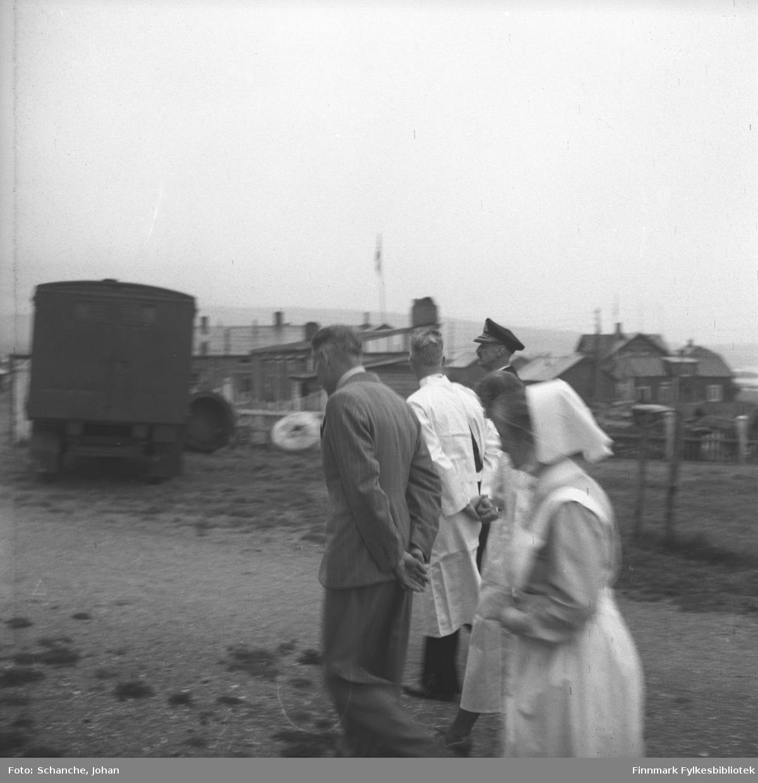 Kongebesøk:  Kong Haakon VII besøker sykehuset i Vadsø. Kongen  går med overlege Bjarne Skogsholm, oversøster Anna Aase og leder Langseth på gata forbi en sykebil.  Den gamle militærsykebilen var i bruk i Vadsø etter krigen tros for at den stadig hadde problemer med å starte. På bakgrunn ses en del av byen.  Bildet er litt uskarp.