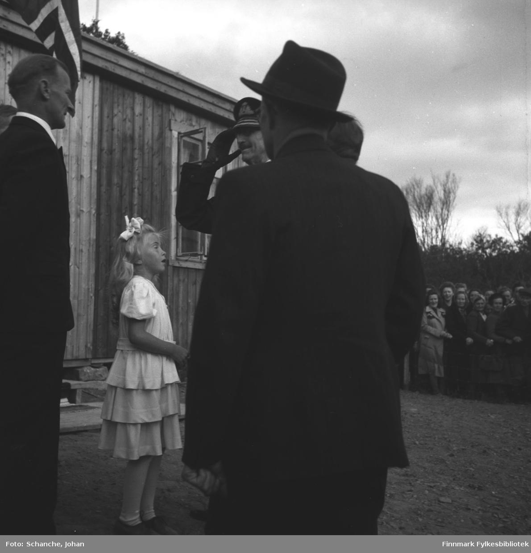 Kongebesøk i 1946:  Kong Haakon VII besøker Tana. Kongen hilser en mann som står halveis med ryggen mot kamera. Foran Kongen står en annen mann slik att vi ser bare ansiktet og hander til Kongen på bildet.  Mellom mennene står en liten jente på hvit kjole, hun har antagelig gitt blomsterbuketten til Kongen.