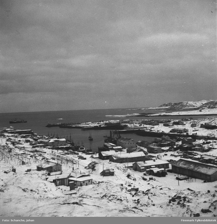 Oversiktsbilde fra Berlevåg i gjenreisningstid.  På bildet ses nesten hele byen slik den var 1948. Bildet er tatt fra fjellet. Noen båter ligger på kai, et skip ut i havet.