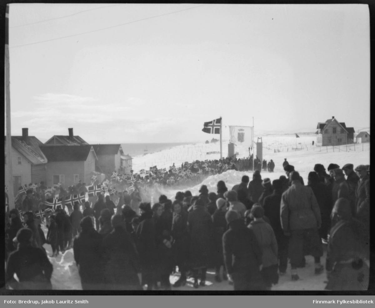 Fra kronprinsparets besøk i Vadsø 1934. I følge Finmarkens amtstidende ankom kronprinsparet Vadsø med Polarbils biler kl. 3 i strålende sol. Paret ble møtt med en æresport og flaggborg ved Prestelva, der skolens elever og speiderne dannet espalier langs Nyborgveien og inn mot byen. Været var bra, slik at turen fra Prestelv ble foretatt i slede. En masse mennesker var møtt fram, og byen var pyntet med flagg. Etter ankomsten til fylkesgården hilste kronprinsparet fra verandaen barnetoget som marsjerte forbi. Om kvelden kl. 91/2 gikk der fakkeltog fra Ørtangen med 200 fakler og hornmusikk opp til fylkesgården hvor ordfører Rasmussen holdt en kort velkomsttale og utbragte et leve for kronprinsparet. Toget hadde samlet omkring 1500 mennesker. Fredag formiddag var kronprinsparet ute på havnen og så på loddenøtene som akkurat nu stod fulle av lodde. I Festivitetslokalet hadde borgerne arrangert en tekonsert hvortil de kongelige var innbudt. Der var konsert av orkesteret 'Fremad' og sang av barnekoret.  Billettene til konserten var solgt ut på en time.  Sorenskriver Bredrup holdt her velkomsttalen for de kongelige høyheter. Han overrakte derefter kronprinsparet et Finnmarksbillede malt av kunst. Ivar Sælø.  Ordføreren forestilte for kronprinsparet en rekke av byens folk av alle stender. Efterat ordføreren hadde takket de kongelige og deres følge for samværet med byens borgere, holdt kronprinsen en tale for byen og uttalte de beste ønsker for dens næringsliv og dens fremtid og trivsel. Klokken 3 var det middag i fylkesgården for byens autoriteter og embedsmenn med fruer.  Avreisen til Kirkenes foregikk til fastsatt tid kl. 6 med hurtigruten 'Prinsesse Ragnhild'.  Idet båten la fra kaien takket ordføreren for besøket i Vadsø og under den store folkemengdes veldige hurraer, dampet båten med de kongelige ut av havnen. De kongeliges besøk i Vadsø forløp på en for byen verdig og særlig vellykket måte. Og vi tror de kongelige fikk et godt inntrykk i fra byen ved Varangerfjorden. P