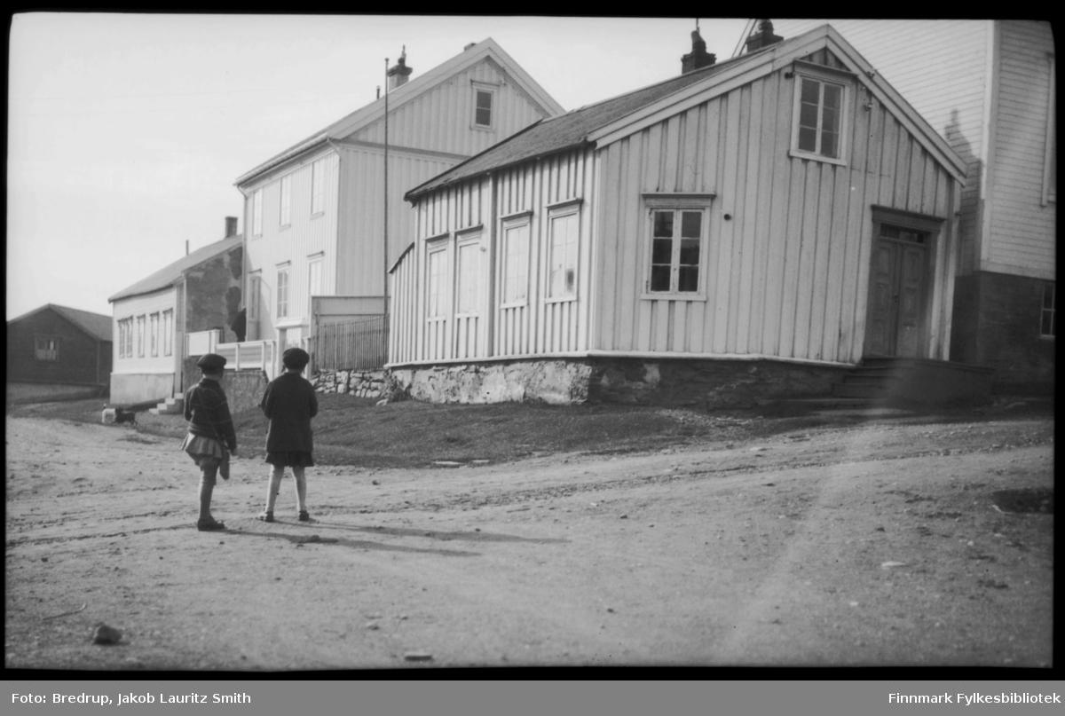 To jenter står i Kirkegata (Kirkebakken) i Vadsø og betrakter to hunder som leker.  Fotografen har stått i det vi tror var Inspektør Hansens gate og fotografert nedover gata. Bolighus på øversiden av veien, huset nærmest kamera var Indremisjonens hus.