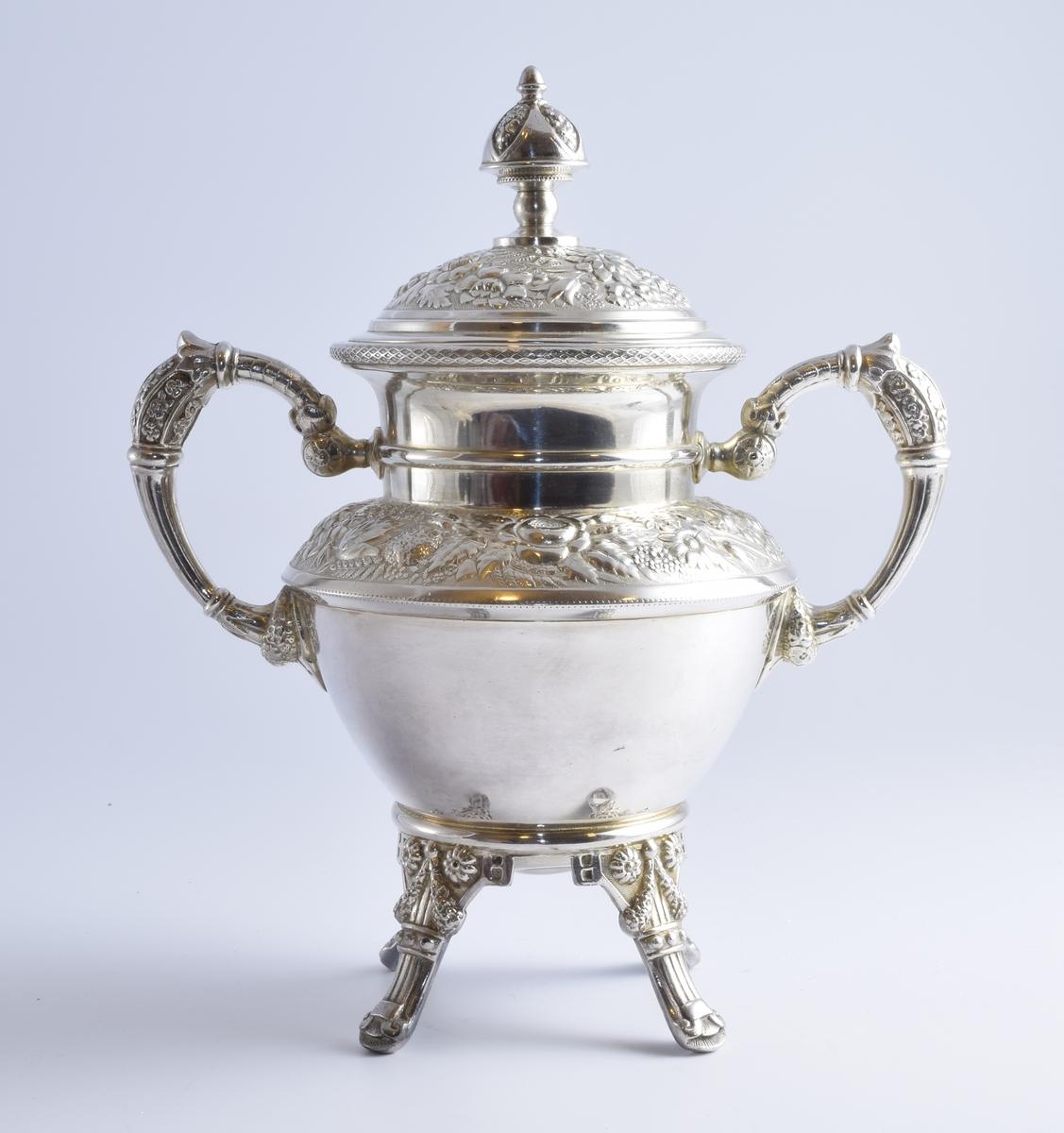 Sukkerskål med lokk i sølvplett med blomstermotiv. Skålen er del av et sett med to kanner og en fløtemugge.