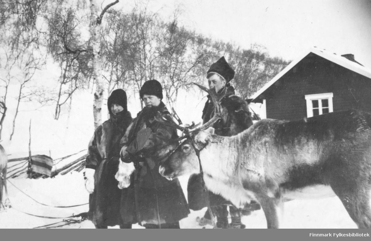 Tre personer og et reinsdyr fotografert utenfor et hus ved Levajok fjellstue. Alle tre er kledd i pesker. I kanten til venstre på bildet er det et reinsdyr til, og man kan se føttene på en fjerde person bak de andre tre. I bakgunnen er det også en skigard.