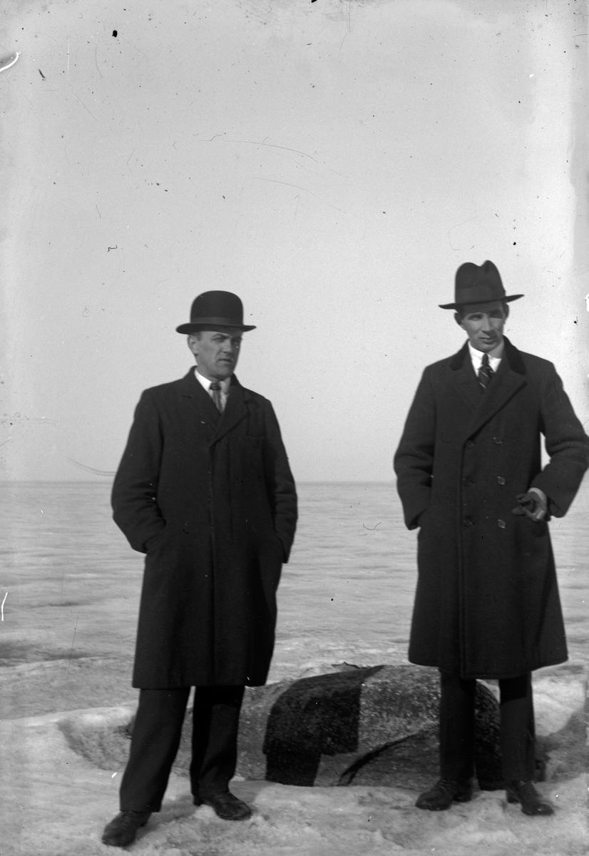 Två män i rock och hatt står vid en isbelagd sjö.