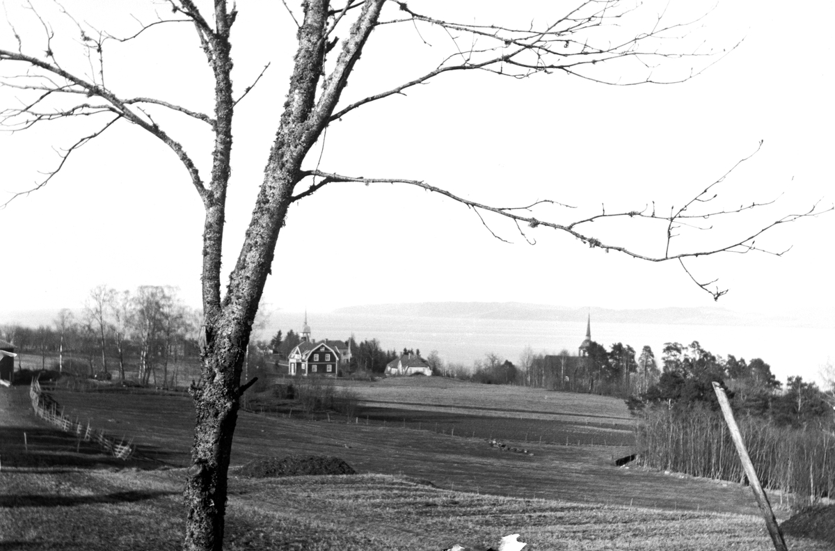 Fält, gård och Bäckaby kyrka med utsikt över Jönköping och Vättern.