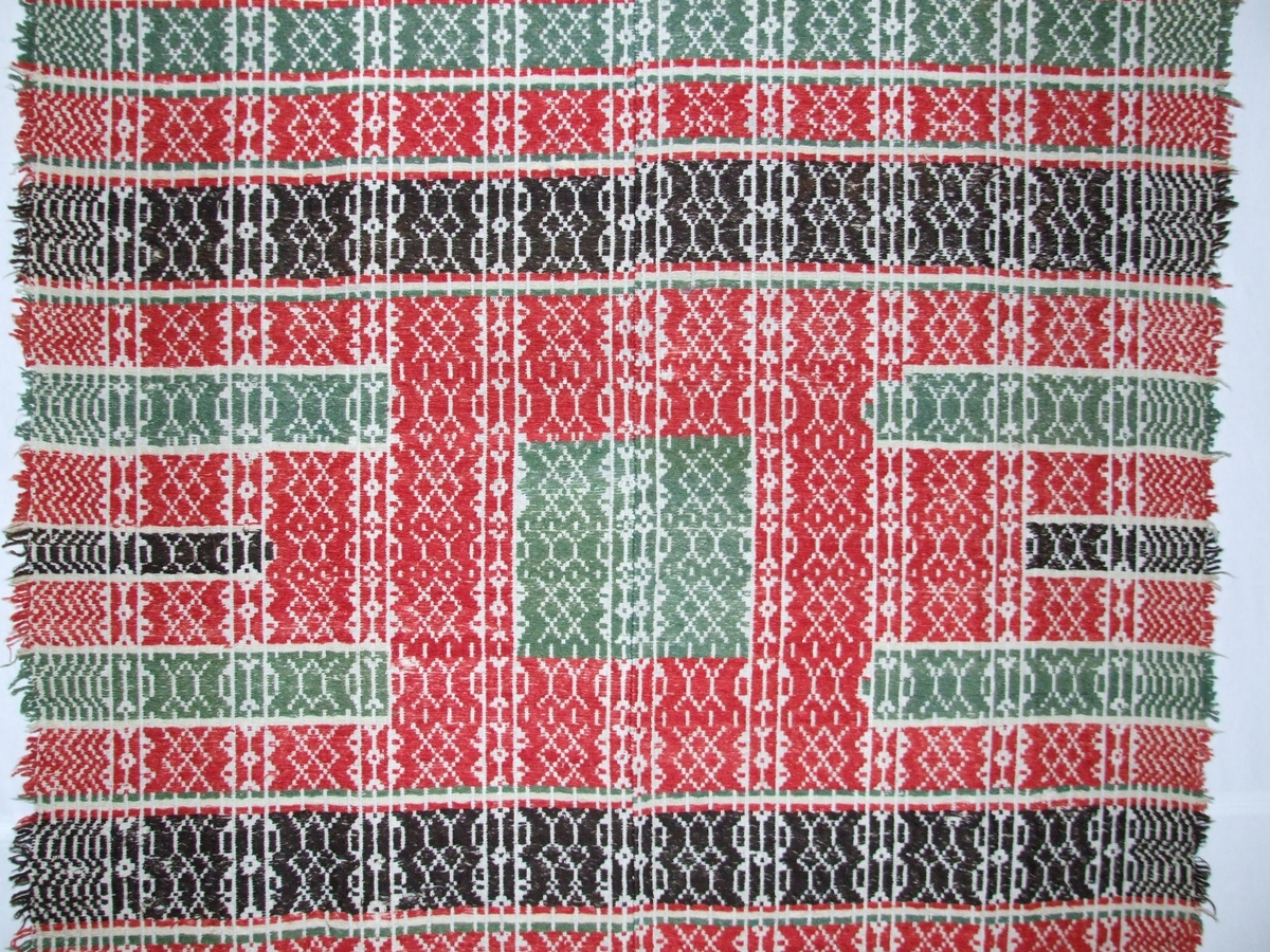 Mønster i striper. Grøn firkant med raud kant rundt i midten.