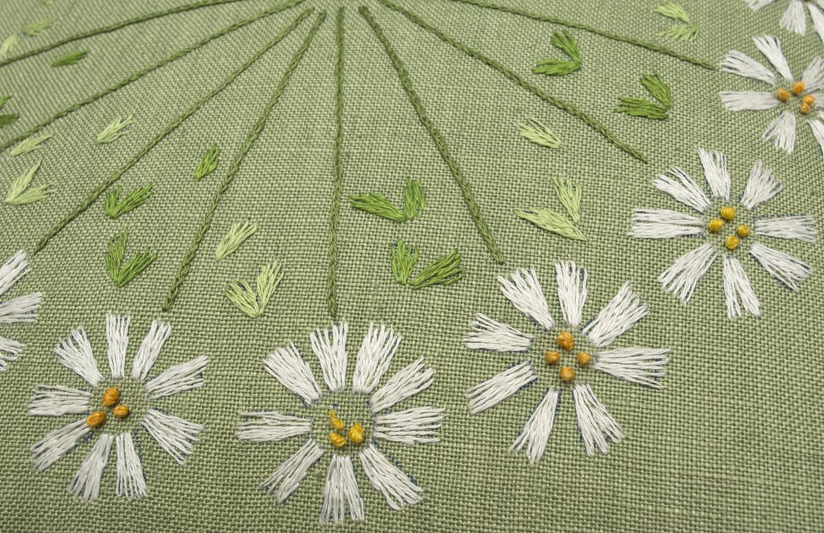 Stoppad kudde. Broderad på ljusgrönt linne (Ölandslinne färg 205) med klyvsöm, kedjesöm och knutsöm i vitt, gult och grönt lingarn. Baldersbrå-blommor på stjälk där blommorna bildar krans och stjälkarna strålar in mot mitten.