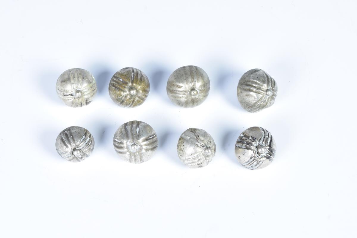 Åtte sølvknapper dekorert med fire felt med parallelle forsenkede linjer som som danner et likearmet kors.