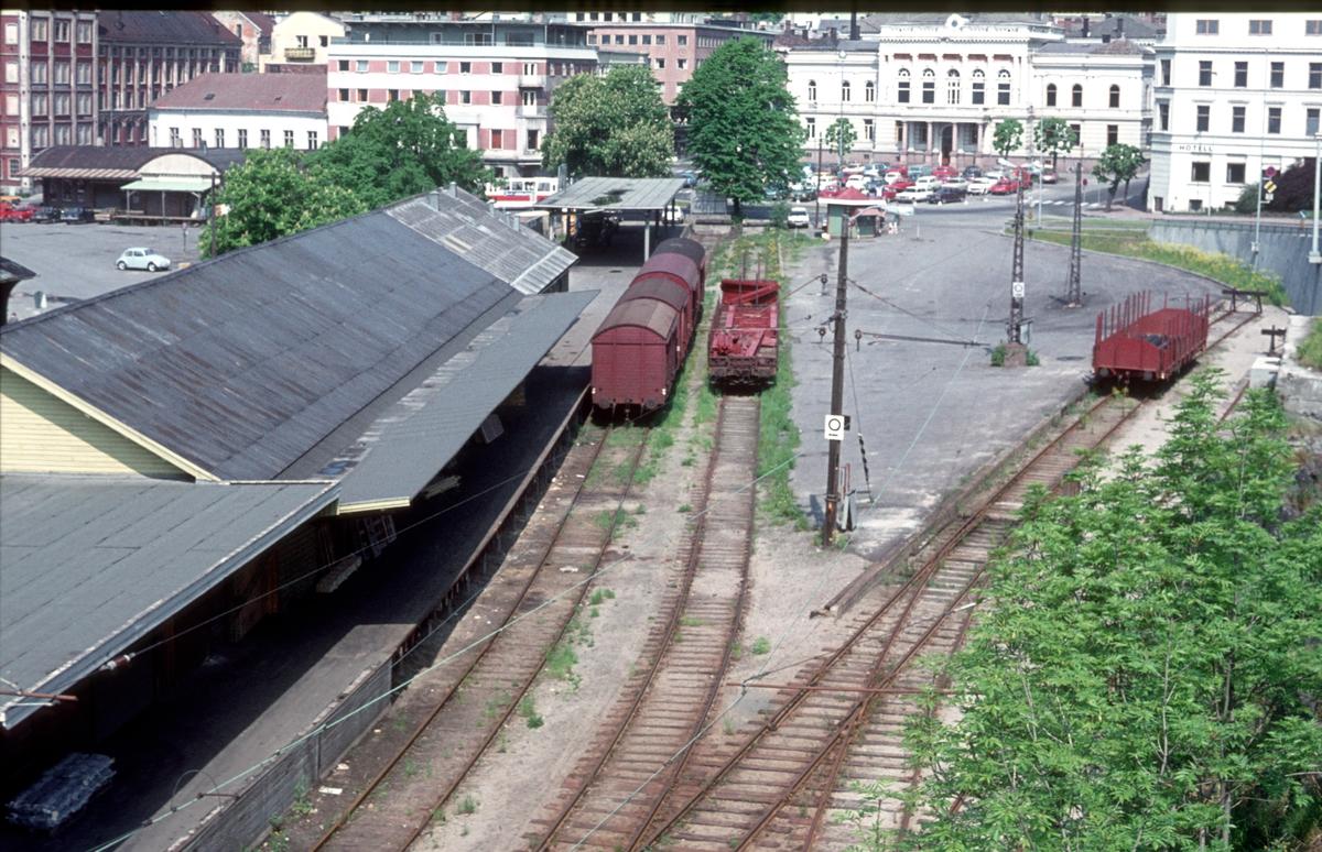 Oversiktsbilde Skien G. (Skien Gamle stasjon). Til høyre ser vi en godsvogn i det som var hovedtogsporet, omtrent rett ut for der stasjonsbygningen var. Til venstre lastespor og godshus. Skien rådhus i bakgrunnen.