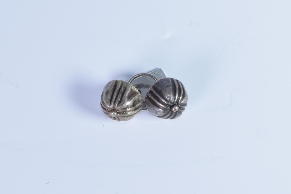To sølvknapper dekorert med fire felt med parallelle forsenkede linjer som som danner et likearmet kors.