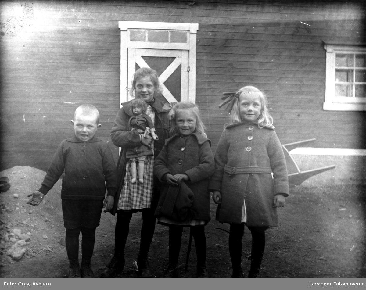 Gruppe, barn med dukke foran uthus