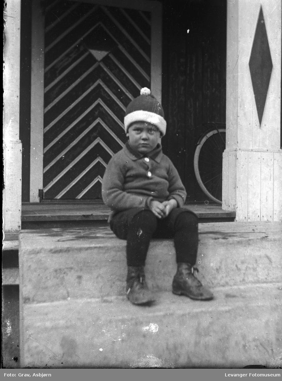 Gutt med topplue på trapp